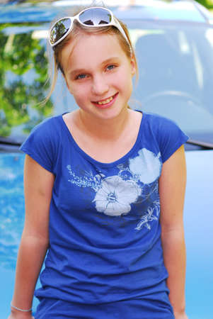 Portrait of a young girl in sunglasses sitting on a car hood
