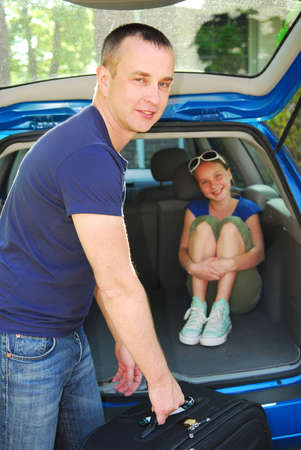 Father loading luggage in a car for a family trip