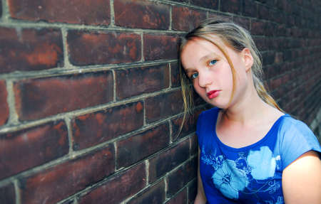 Young girl near brick wall looking upset Stock Photo