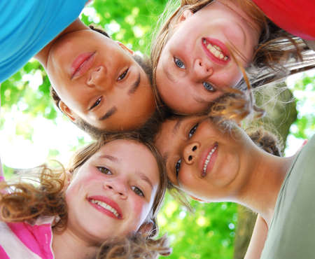 ниже: Faces of four happy young girls shot from below