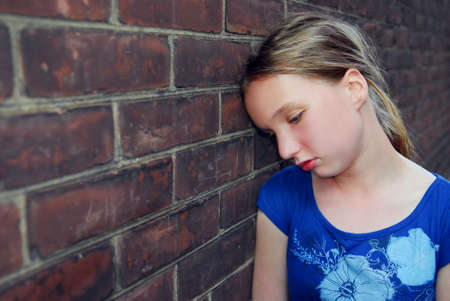 child alone: Young girl near brick wall looking upset Stock Photo