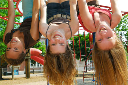 Three young girls hanging upside down in a park and laughing photo