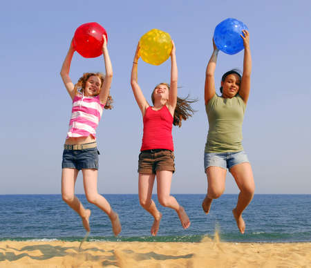 Three girls on a sandy beach jumping with colorful balls Stock Photo