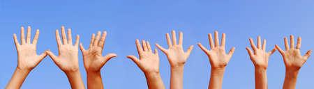 manos levantadas al cielo: L�nea de las manos con las palmas abiertas sobre el cielo azul de fondo  Foto de archivo