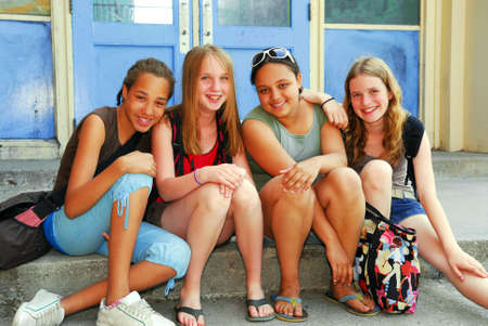 preteen girls: Portrait of a group of young smiling school girls sitting on steps near school building