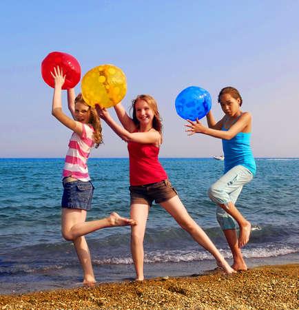 Drie meisjes met kleurrijke strand ballen lopen op zee  Stockfoto