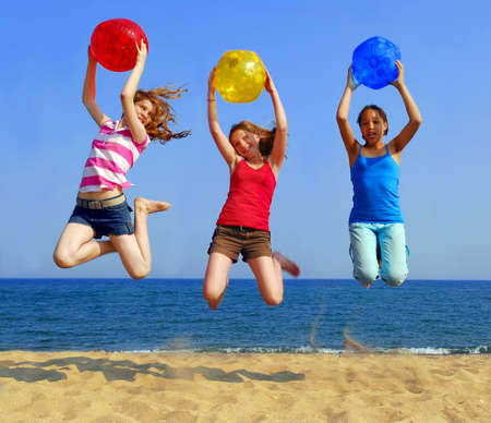 Three girls with colorful beach balls jumping on a seashore photo