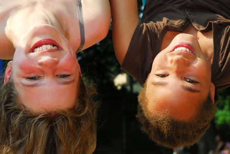 Two girls hanging upside down in a playground