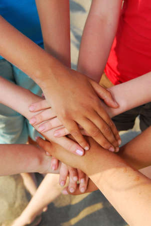 diverse hands: Hands of diverse group of teenagers joined in union Stock Photo