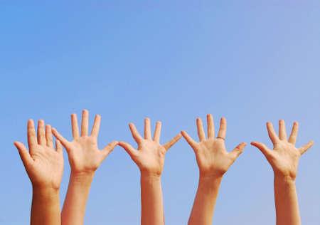 manos levantadas al cielo: Criado en manos de fondo azul cielo con copia espacio  Foto de archivo