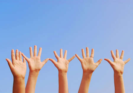 Raised hands on blue sky background with copy space