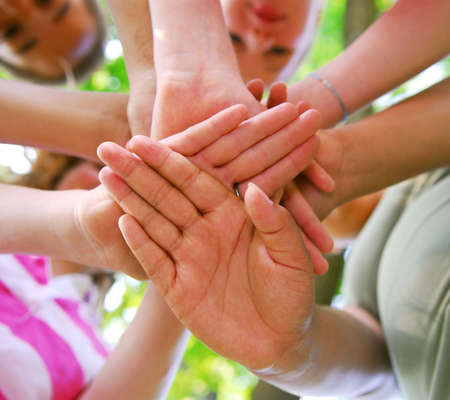 hands joined: Hands of diverse group of teenagers joined in union Stock Photo