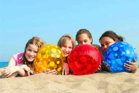 Portrait of four young girls with colorful beach balls