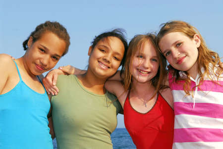 preteens beach: Portrait of four smiling teenage girls outside Stock Photo