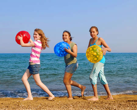 Three girls with colorful beach balls walking on sea shore photo