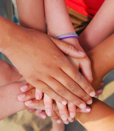 joining together: Hands of diverse group of teenagers joined in union Stock Photo