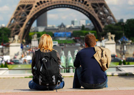 Young tourist couple sitting in front of Eiffel tower in Paris France photo