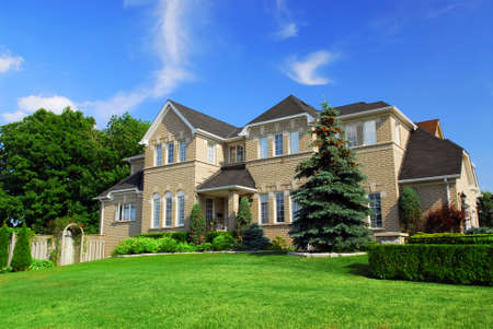 frontyard: Large upscale residential home with bright green lawn and blue sky