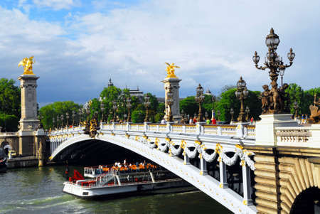 Alexander the Third bridge and Seine cruise boat in Paris, France. Imagens