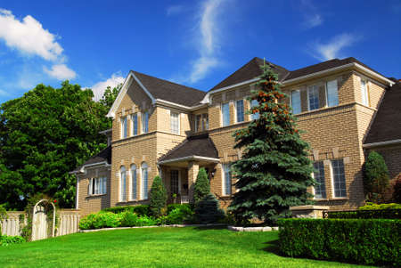 upscale: Large upscale residential home with bright green lawn and blue sky