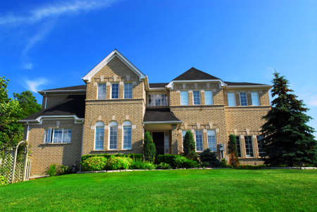 affluence: Large upscale residential home with bright green lawn and blue sky
