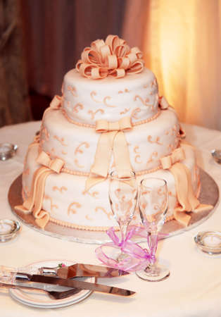 three   layer: Three tiered wedding cake and champagne glasses on a table Stock Photo