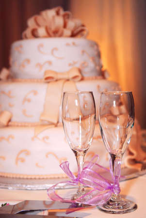 Three tiered wedding cake and champagne glasses on a table photo