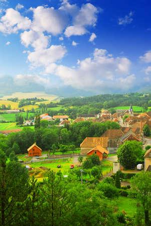 Paisaje rural, con colinas y un pequeño pueblo en el este de Francia Foto de archivo