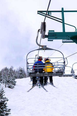 Skiers wearing funny hats on a chairlift in snowy mountains Stock Photo - 1353518