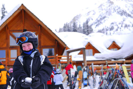 Young girl in ski gear holding a snowball at downhill skiing resort photo