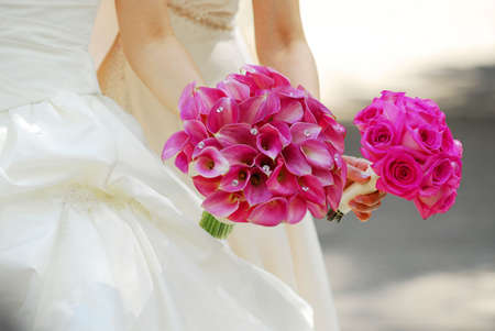 Bride and bridesmaid holding bouquets of pink flowers photo