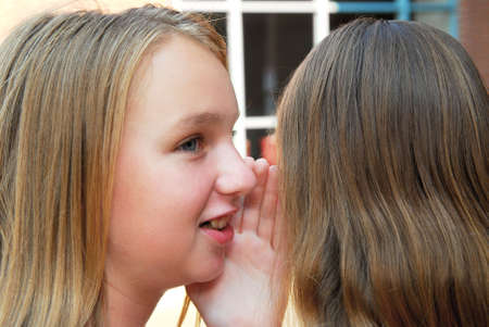 confide: Two young teenage girls gossiping in school yard Stock Photo