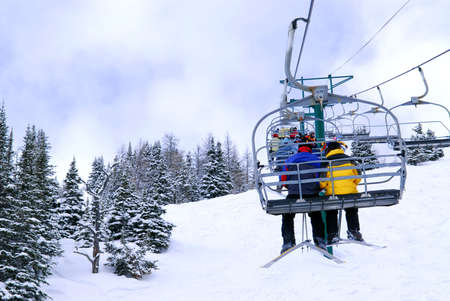 Skiers wearing funny hats on a chairlift in snowy mountains Stock Photo - 1364620