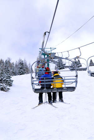 Skiers wearing funny hats on a chairlift in snowy mountains Stock Photo - 1404715
