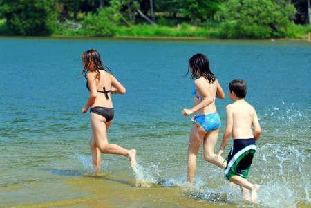 ba�arse: Grupo de ni�os peque�os en el agua corriendo en la playa