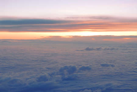 rise above: Spectacular view of a sunset above the clouds from airplane window