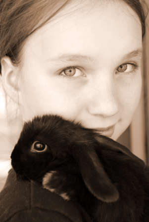 Portrait of a young girl holding a black  rabbit in sepia photo
