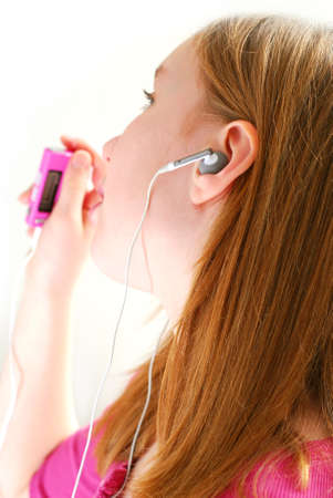 dance preteen: Young girl listening to music on her mp3 player white background Stock Photo