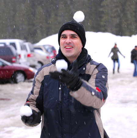 Happy man juggling snowballs in winter park photo