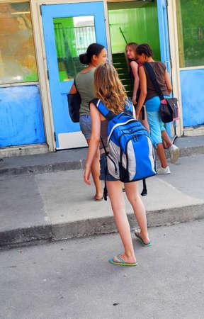 学校の建物に入る若い女の子のグループ