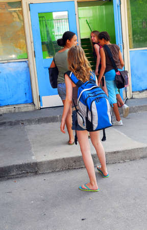 Group of young girls entering school building Stock Photo