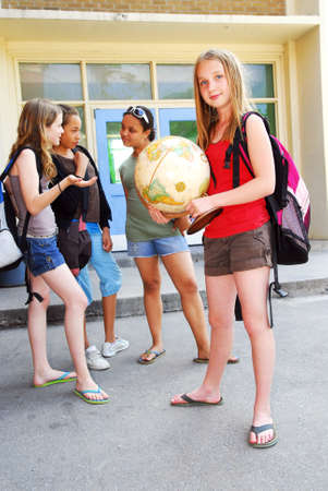 preteens girl: Group of young girls near school building Stock Photo