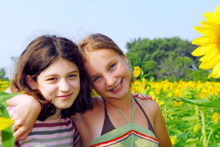 preteens girl: Portrait of two young girls in a sunflower field