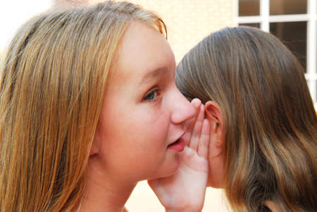 confiding: Two young teenage girls gossiping in school yard Stock Photo