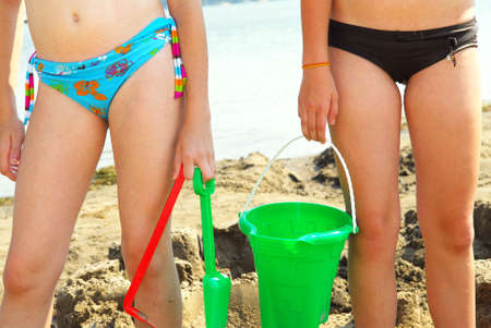 Preteen girls building a sand castle on a beach