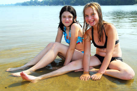 Two preteen girls sitting in shallow water on a beach