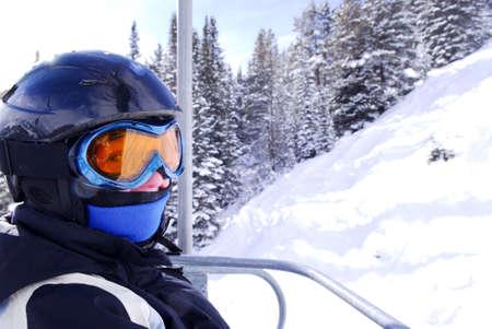 riding helmet: Chica en artes de esqu� cuesta abajo en un telesilla en la estaci�n de esqu�
