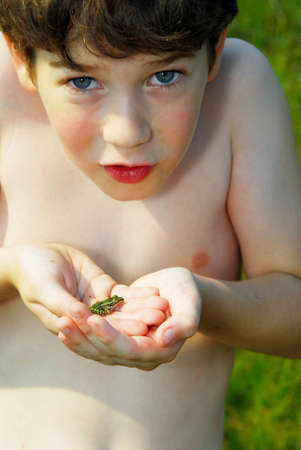 Young boy holding a tiny frog in his hands Stock Photo