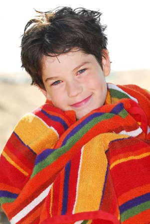 Young boy wrapped in a towel on a beach relaxing after swimming photo
