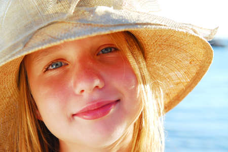 Portrait of a teenage girl wearing straw hat on a beach photo